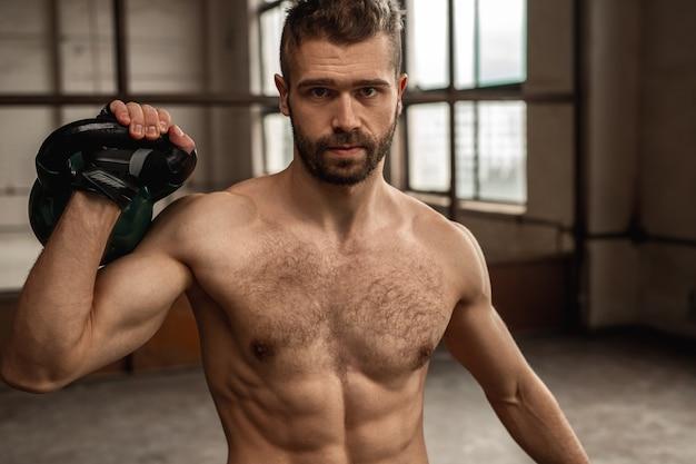 Zelfverzekerde brute bebaarde shirtless man met gespierde torso zware kettlebell opheffen en kijken tijdens intensieve gewichtheffen training in de sportschool