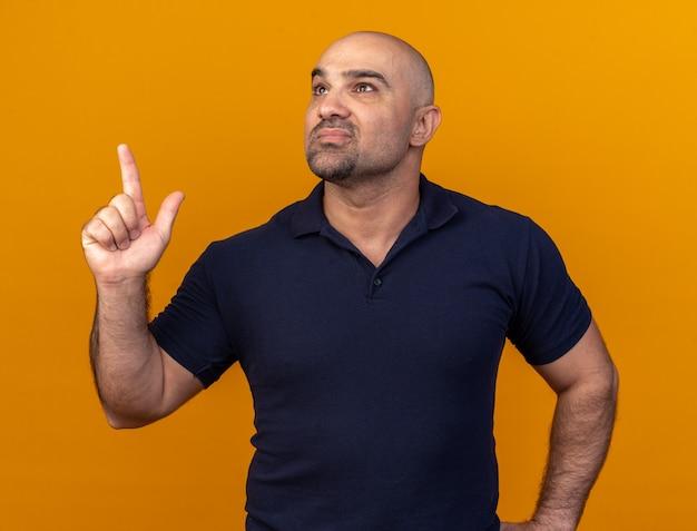 Zelfverzekerde casual man van middelbare leeftijd die de hand op de taille houdt en omhoog wijst, geïsoleerd op een oranje muur