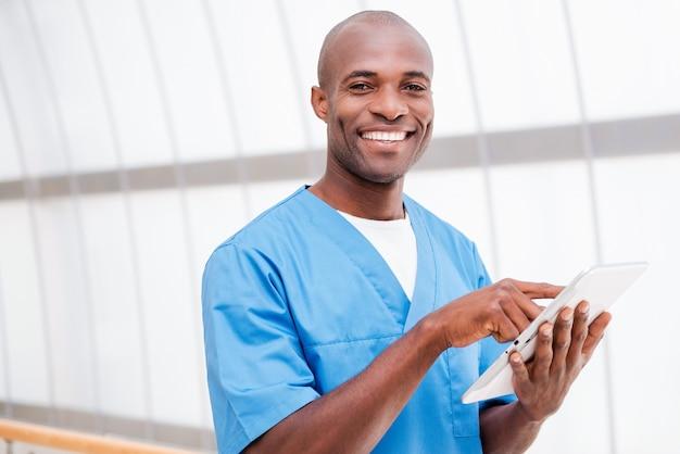 Zelfverzekerde chirurg. vrolijke jonge afrikaanse arts in blauw uniform die aan digitale tablet werkt en glimlacht