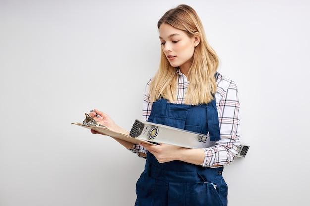 Zelfverzekerde constructor vrouw met niveaugereedschap en papieren klembord document in handen geïsoleerd op witte studio achtergrond