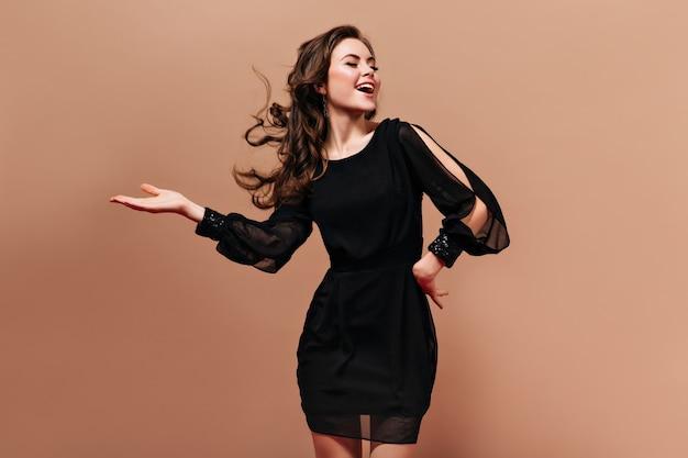 Zelfverzekerde dame in korte zwarte jurk lacht en speelt haar haren op beige achtergrond.