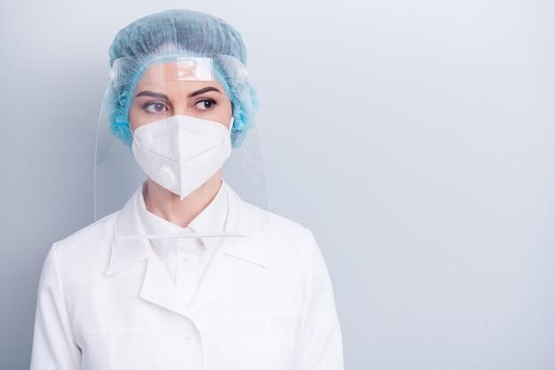Zelfverzekerde doktersdame draagt een beschermend medisch maskerschild geïsoleerd op een grijze muur