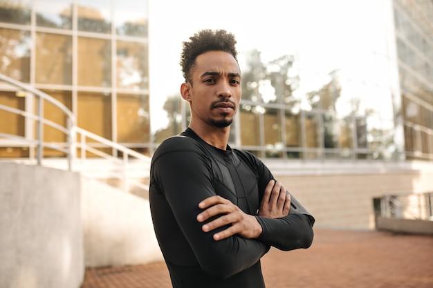 Zelfverzekerde donkerbruine sportman in zwart t-shirt met lange mouwen kruist armen, kijkt in de camera en poseert buiten