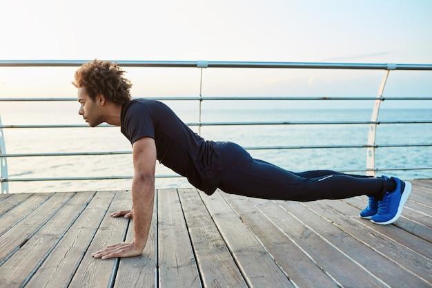 Zelfverzekerde donkere gespierde jonge sportman die sportslijtage draagt en plankpositie doet tijdens het trainen op de houten vloer van de dijk. 's morgens vroeg aan zee sporten