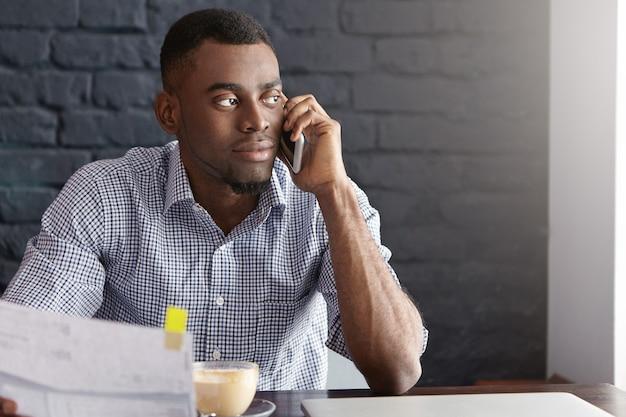 Zelfverzekerde donkere zakenman met stuk papier in de ene hand en mobiele telefoon in andere
