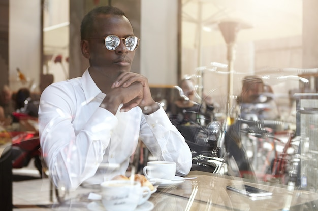 Zelfverzekerde doordachte jonge afro-amerikaanse zakenman in stijlvolle brillen handen omklemde zittend in de coffeeshop met mok op tafel, kwam na te denken over zakelijke problemen over kopje cappuccino