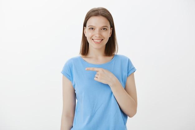 Zelfverzekerde en assertieve glimlachende vrouw die uitcheckgebeurtenis uitnodigt, wijzende vinger naar links