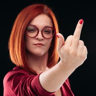 Zelfverzekerde en boze roodharige vrouw die vinger toont, fuck off.