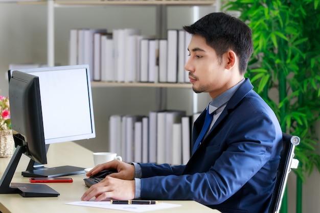 Zelfverzekerde en gelukkige jonge aziatische zakenman die werkt aan de bedrijfsstrategie in zijn privékantoor. bedrijfs- en succesconcept.