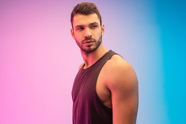Zelfverzekerde en gerichte bebaarde europese jongeman. knappe kerel draagt tanktop. geïsoleerd op blauwe en roze achtergrond. studio opname. ruimte kopiëren