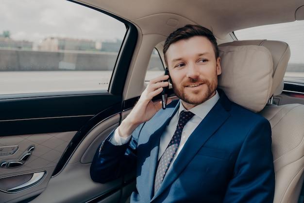 Zelfverzekerde en knappe jonge mannelijke bedrijfsmedewerker in klassieke outfit stijlvol pak praten op mobiele telefoon, genieten van zakelijk gesprek zittend op de achterbank van luxe auto en naar kantoor gaan