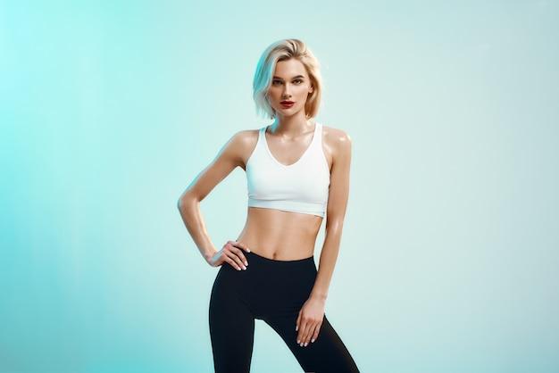 Zelfverzekerde en mooie sexy jonge vrouw in witte top en zwarte legging die arm aanhoudt