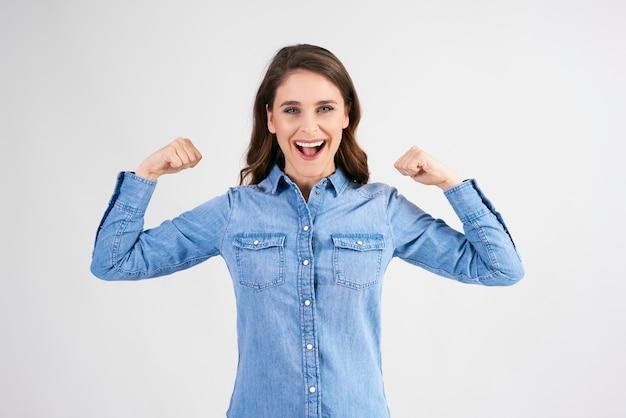 Zelfverzekerde en sterke vrouw die haar biceps laat zien