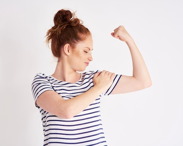 Zelfverzekerde en sterke vrouw die haar bicepsschot laat zien