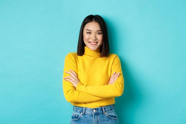 Zelfverzekerde en stijlvolle aziatische vrouw kruist de armen op de borst en glimlacht, staande over een blauwe achtergrond.