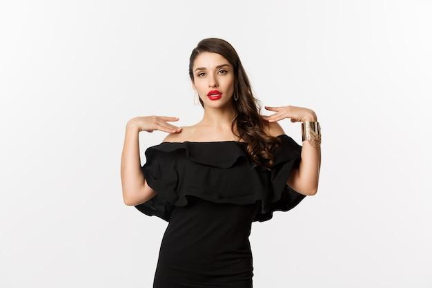 Zelfverzekerde en stijlvolle vrouw in zwarte elegante jurk, brutaal kijken naar camera, staande op witte achtergrond.