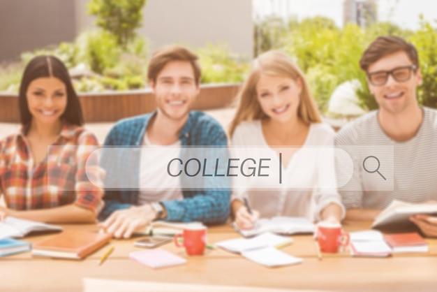 Zelfverzekerde en succesvolle studenten. groep gelukkige jonge mensen die samenwerken en naar de camera kijken terwijl ze buiten aan het houten bureau zitten