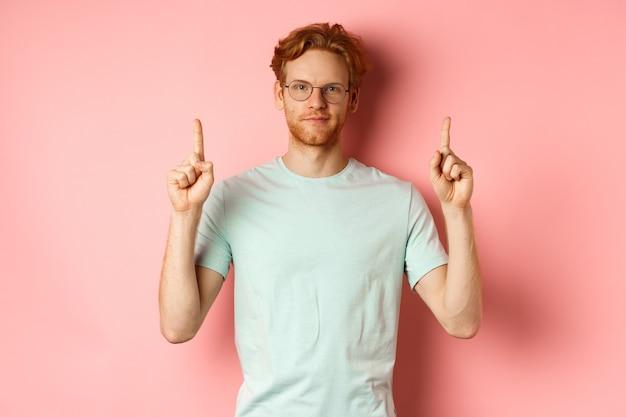Zelfverzekerde en tevreden jongeman met rood haar, bril en t-shirt, vingers omhoog wijzend en lachend met zelfvoldaan gezicht, goede deal laten zien, staande over roze achtergrond.