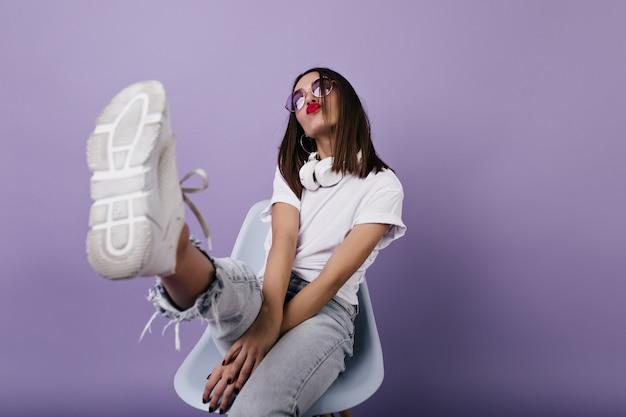Zelfverzekerde europese dame in witte sneakers zittend op een stoel en gezichten trekken. portret van prachtig meisje poseren.