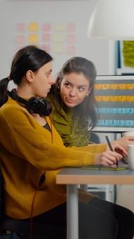 Zelfverzekerde foto-editors voor vrouwen zitten op de werkplek in creatieve studio
