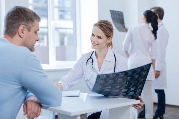 Zelfverzekerde gekwalificeerde vriendelijke neuroloog die geniet van een afspraak met de patiënt en de mrt-scan analyseert terwijl collega's genieten van het bespreken achter