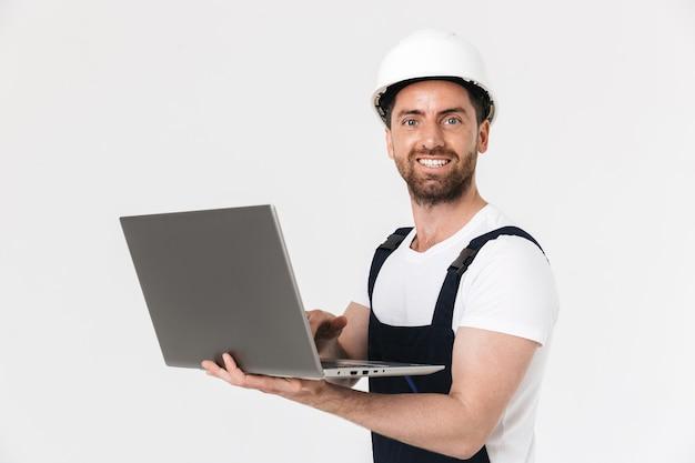 Zelfverzekerde gelukkige bebaarde bouwman met een overall en veiligheidshelm die geïsoleerd over een witte muur staat, met behulp van een laptopcomputer