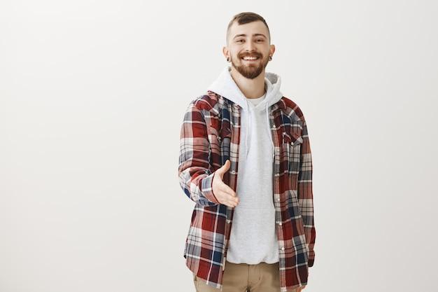 Zelfverzekerde gelukkige hipster strekt zijn hand uit voor een handdruk en groet iemand