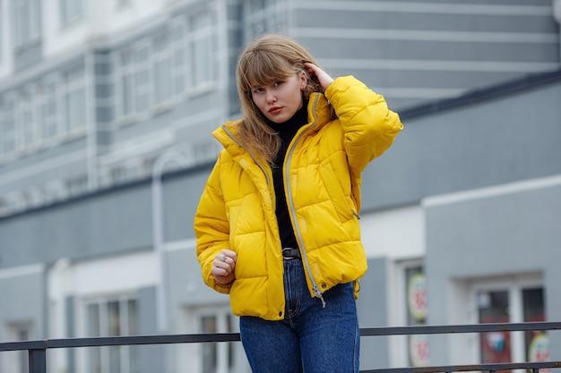 Zelfverzekerde gelukkige mooie jonge hipstervrouw die een geel jasje draagt dat zich op stadsstraat bevindt