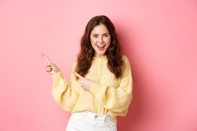Zelfverzekerde gelukkige vrouw met krullend kapsel, wijzende vingers opzij, promo op linker copyspace, opgewonden glimlachend, staande over roze muur.