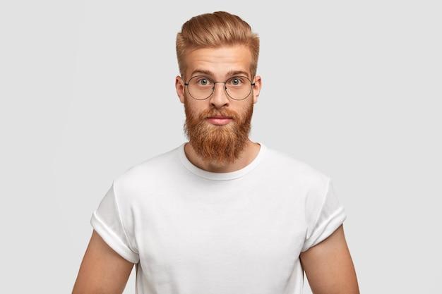 Zelfverzekerde gember man met trendy kapsel, bril draagt, ziet er direct uit