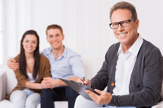 Zelfverzekerde gezinspsycholoog. zelfverzekerde psychiater die iets op het klembord schrijft en glimlacht terwijl een vrolijk stel op de achtergrond zit en handen vasthoudt