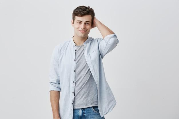 Zelfverzekerde glimlachende blanke man, met donker haar en aantrekkelijke blauwe ogen, kijkend met tevreden uitdrukking, gekleed in een blauw shirt over een t-shirt, met zijn hand achter de achterkant van zijn hoofd.