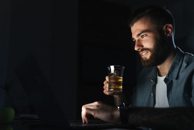 Zelfverzekerde glimlachende jonge man die op een laptop werkt terwijl hij 's nachts binnenshuis aan tafel zit en water drinkt