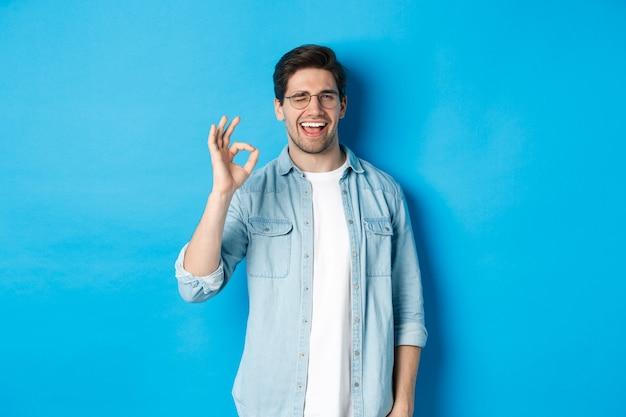 Zelfverzekerde glimlachende man met een bril die een ok teken toont, knipoogt om iets te garanderen of aan te bevelen, blauwe achtergrond.