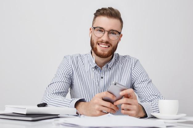 Zelfverzekerde glimlachende man met een specifiek uiterlijk, formeel gekleed, luistert naar audiotrack terwijl hij op de werkplek zit,