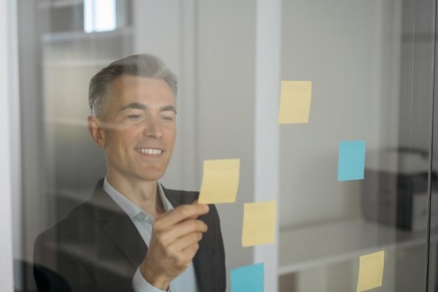 Zelfverzekerde glimlachende scrummaster met behulp van plaknotities, scrum voor productiviteit