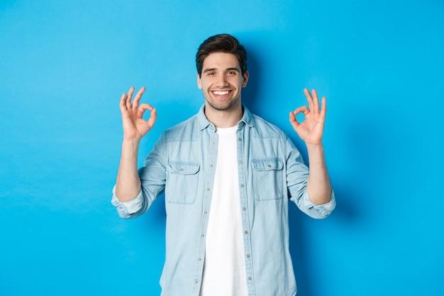 Zelfverzekerde glimlachende volwassen man, die ok tekens toont en er tevreden uitziet, als iets, staande tegen een blauwe achtergrond.