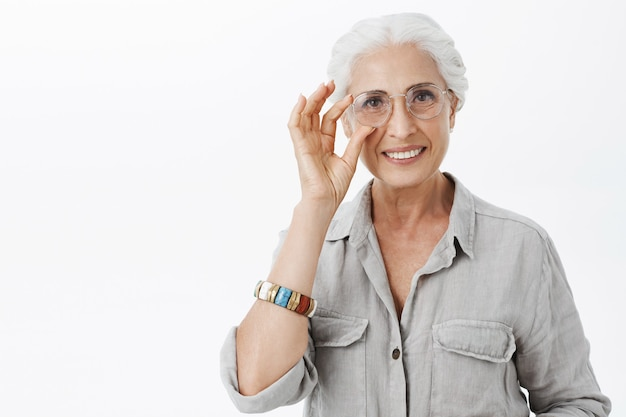 Zelfverzekerde glimlachende vrij oude dame die in glazen tevreden kijkt