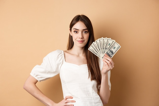 Zelfverzekerde glimlachende vrouw die dollarbiljetten toont, geld verdient en er tevreden uitziet, staande op beige met contant geld.