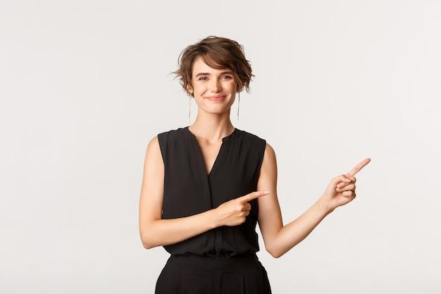 Zelfverzekerde glimlachende zakenvrouw wijzende vingers recht op logo. vrouw die banner over wit toont.