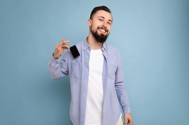 Zelfverzekerde goed uitziende cool lachende brunette bebaarde jonge man dragen stijlvol blauw shirt en wit t-shirt geïsoleerd over blauwe achtergrond muur met creditcard camera kijken