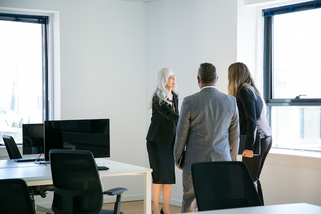 Zelfverzekerde grijsharige zakenvrouw groeten collega's in kantoor. professionele manager handenschudden, glimlachen en samenkomen voor bespreking van project. bedrijfs- en communicatieconcept