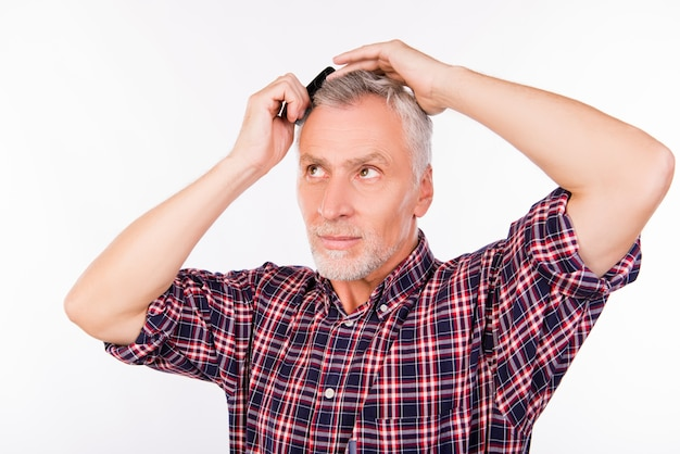 Zelfverzekerde grijze oude man haar kammen