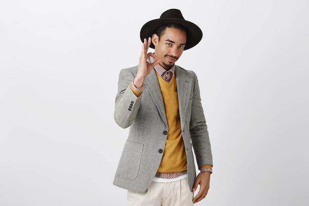 Zelfverzekerde heer zal elk probleem oplossen. zelfverzekerde knappe man in luxe outfit en zwarte hoed, staand in coole pose en goedkeuring met goed teken