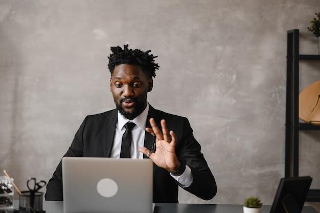 Zelfverzekerde jonge afrikaanse man kijkt naar videobellen via webcamconferenties op kantoor