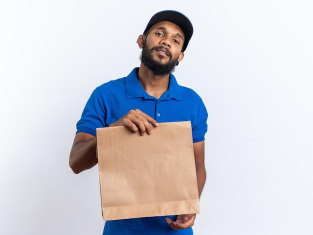 Zelfverzekerde jonge afro-amerikaanse bezorger die een voedselpakket vasthoudt dat op een witte muur met kopieerruimte wordt geïsoleerd