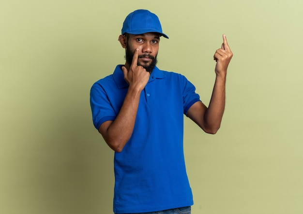 Zelfverzekerde jonge afro-amerikaanse bezorger die zijn ooglid naar beneden trekt en omhoog wijst geïsoleerd op olijfgroene achtergrond met kopieerruimte