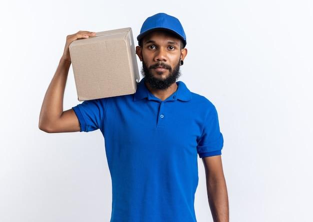 Zelfverzekerde jonge afro-amerikaanse bezorger met kartonnen doos op zijn schouder geïsoleerd op een witte achtergrond met kopieerruimte