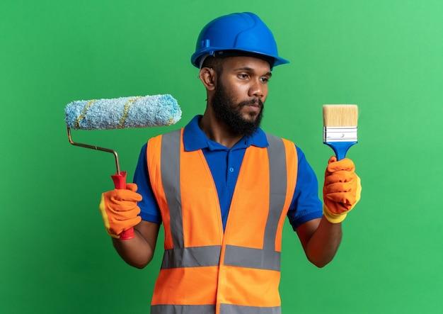 Zelfverzekerde jonge afro-amerikaanse bouwer man in uniform met veiligheidshelm en handschoenen houden verfroller en kijken naar kwast geïsoleerd op groene achtergrond met kopie ruimte