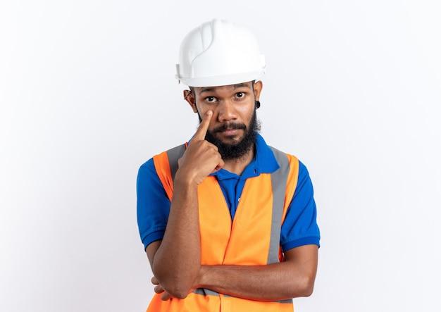 Zelfverzekerde jonge afro-amerikaanse bouwer man in uniform met veiligheidshelm naar beneden te trekken ooglid met vinger geïsoleerd op een witte muur met kopie ruimte